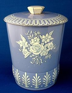 This is a tea tin, tea caddy or tea canister made in England by Daher or Baret with a blue and white floral design reminiscent of Wedgwood jasperware. This is a shape and design made by both companies in the 1950-1960s.