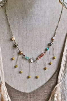 Oh so boho chic..  features assorted glass beads,gemstones,baroque pearl,rhinestone bead,crystal,antique brass chain. It closes with a lobster