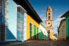 Buildings of vivid color lead to Saint Francis's church and monastery near Plaza Mayor in Trinidad.