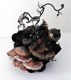 Amy Gross uses hand stitchery, paper, polymer clay and seed beads to mimic objects from nature, as seen in this piece featuring lichens