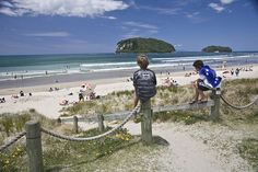 29 December Two teenage boys sit on wooden poles and look out onto the beach. Whangamata, Coromandel, New Zealand. New Zealand Beach, British Isles, Kiwi, Beaches, Backyard, Book, Summer, Travel, Patio