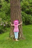 BCP820-15 Woman in festive pink hat hugging tree