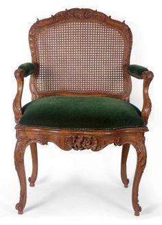 Exceptionnel fauteuil en bois naturel sculpté et à large dossier plat, garni de canne, sculpté sur les quatre faces. Début de l'époque Louis XV.