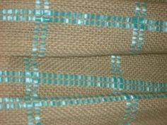 Manta de bebe tejida en telar con aplicaciones de cintitas de raso.