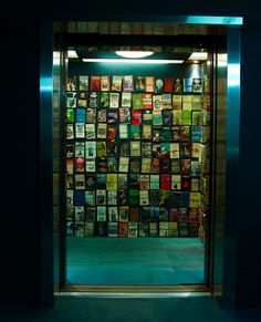 an elevator lined with seventies adventure paperbacks. studio Toogood The Voyage of Discovery project at Selfridges.