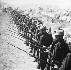 Photograph:Soldiers in the Spanish-American War stand ready to defend their camp.