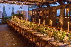 Beautiful long table for 40 decorated with green and white florals, brass candlesticks, and lit tapers.