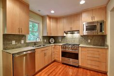 This stylish kitchen features beautiful light wood cabinetry and opens up to the dining room, but cabinets were installed between the two rooms to provide ample double-sided storage and countertop space for serving. A warm-toned hardwood floor offers both a welcome contrast to and complements the light cabinetry.