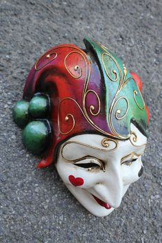 """""""Kings Fool"""" - face mask model in red/green variation with white face and playing card symbols on cheeks."""