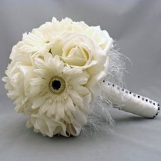 This bouquet is a timeless classic with a splash of modern flair thrown in. It's made from roses and calla lilies with fringe added as a skirt. The stems are wrapped in satin ribbon and accented with black and white decorative floral pins for contrast. Daisy Bridal Bouquet, Blush Pink Wedding Flowers, Spring Wedding Flowers, Wedding Table Flowers, Rustic Wedding Centerpieces, Wedding Bouquets, Daisy Wedding, Rustic Weddings, Rose Bouquet