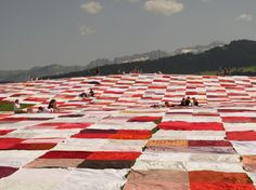 Frank and Patrik Riklin, [giant picnic blanket], Stein, Switzerland, 2014.  The super-sized feat, 160,000 feet of comfy, ant-resistant goodness, was sewn together from recycled towels, curtains, sheets and tablecloths, all donated by the local community. The setting gave way to a massive family-friendly art feast, with 1,500 visitors bringing sunscreen and snacks to the novel art event.