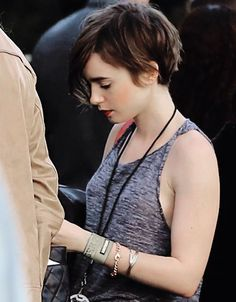 Lily Collins sifts through her bag as she arrives at the U2 Concert held at The Forum, May 31