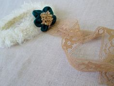 Textured cream colored newborn halo with a teal and gold flower and trailing antique lace.