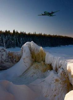 Ice Pilots: A Buffalo Airways DC-4 makes its way over the frozen expanse of Alexandra Falls in the Northwest Territories. Photo credit: John Driftmier