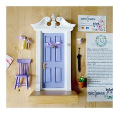 Delicate Fairy Door with lovely shades of purple. This unique Fairy Door is a real piece of art. With a neoclassical frame painted in white whit a double coat of satin varnish and a sweet lilac color for the door, it is sure to compliment any decor. On its large wooden porch, the lucky new fairy owner will benefit from a cozy little purple chair with hand painted details, a useful black umbrella for rainy days, a flowery porcelain cup (empty), and a little terra cotta pot o porch with white…