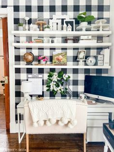 Black and white modern office with white narrow desk, black and white buffalo check wallpaper and white floating shelves.