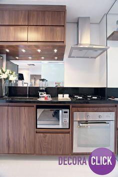 A madeira escura na cozinha fica linda! Observem o contraste criado com os eletrônicos em inox e a pedra da pia preta.