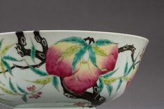 A famille-rose peach bowl from Qing Dynasty. Open month, arc abdomen sits on a shallow ring foot. The exterior decorated with peaches hanging on a tree with flowers next to them. The bottom of the bowl marked with Guang Xu Nian Zhi.