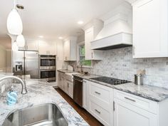 White cabinet kitchen with marble countertops and marble tile backsplash with mini pendant lighting
