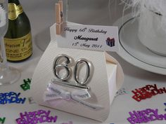 White silk handbag favour box, decorated for 60th birthday, with happy birthday ribbon & personalised label