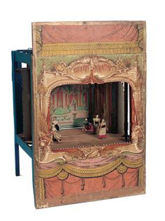 A wooden-framed theatre has richly lithographed design on front fa?ade depicting ornate stage with depictions of Polichinelle and theatrical curtains and instruments; included with the stage are three different back scenes with various side curtains,floor with slits for positioning the five wooden dolls that are included as actresses. Very good condition. French,circa 1880.