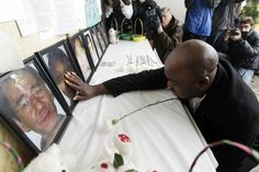 Efanye Chibuko touches a picture of his wife Doris during a memorial service at Oikos University Tuesday, April 10, 2012 in Oakland, Calif. Doris Chibuko was among the victims of a shooting rampage at the Oakland school last week.