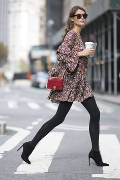 Lais Olivieira in a floral mini dress with black tights and black suede ankle booties. Fall Outfits