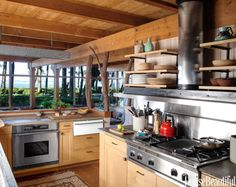 Madrona tree-trunk columns bring the forest outside into the kitchen of a Pacific Northwest house decorated by Markham Roberts. The lower kitchen cabinets continue the warm spirit of wood. A larger version of the living room's galvanized lights hangs above a honed-granite counter and a Dacor oven. Stove top by Thermador.
