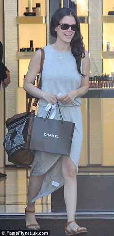 Looking good: She showed off her slender post-baby body in a heather grey sleeveless dress featuring a high-low skirt
