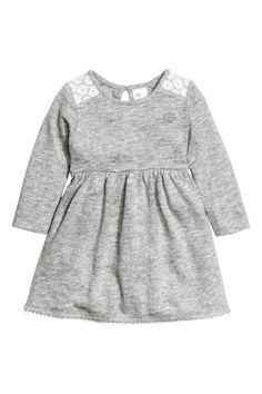Robe en maille fine: Robe en maille fine et souple de coton chiné avec détails en dentelle. Modèle à manches longues avec découpe à la taille. Ouverture surmontée d'un bouton sur la nuque.