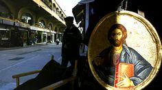 A man walks past a religious icon display in the Monastiraki flea market in Athens