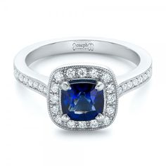This elegant engagement ring features a cushion cut blue sapphire surrounded by a halo of diamonds, with diamond and milgrain accents on the shank as well. Designed and created by Joseph Jewelry Elegant Engagement Rings, Halo Diamond Engagement Ring, Wedding Rings, Pink Sapphire Ring, Fine Jewelry, Jewellery, Unique Rings, Vintage Rings, Pretty Rings