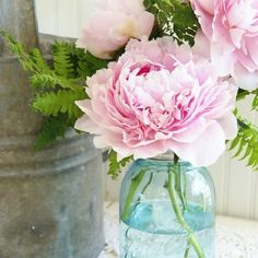 Peonies and ferns in a blue mason jar.
