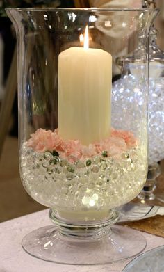 Large hurricane lamp decorated with pink carnations, gel balls and submersible l. Large hurricane lamp decorated with pink carnations, gel balls and submersible lights, with a large pillar candle. Candle Centerpieces, Wedding Centerpieces, Wedding Table, Floral Centerpieces, Floral Arrangements, Diy Wedding, Wedding Decorations, Christmas Decorations, Table Decorations