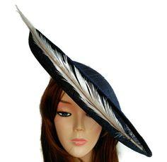 Pamela azul marino. La pamela es azul marino con una forma diferente, curvada, va decorada con una pluma de faisan gris que dibuja el contorno. Kentucky derby attire