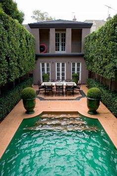 The use of symmetry brings a wow factor to this small space. Tall plantings down both sides off the pool add grandure and cool hard landscape surfaces.