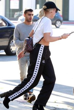 Sofia Richie wearing  Dear Frances Velvet Spirit Boots, Kappa Track Pant, Louis Vuitton Palm Springs Mini Backpack