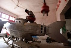 Chinese DIY Inventions - A worker polishes the surface of an unfinished miniature submarine at a workshop of Zhang Wuyi, a local farmer. Basement Workshop, Living In China, Chinese Man, Weird Pictures, Photojournalism, Inventions, Fighter Jets, Remote, Photo Galleries