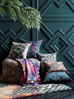 Les couleurs vivent des coussins soulignent l'intensité et la profondeur du bleu canard du mur