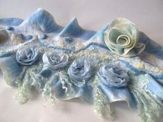 Nuno Felted scarf, Blue ruffle shawl, Nuno felted collar, Blue Wool scarf, Floral Rose shawl wedding scarf This scarf is made of soft merino wool through a Nuno felting process in blue and white colors. Scarf was decorated with fancy yarn , and silk fabric roses The scarf will be delivered with a brooch to fasten it. Size approximately: about 160cm / 30cm (64/12 inches )    Easy care. Hand wash in soap water. Rinse, let it dry.