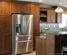 Tall pantry cabinets surround the Stainless Steel refrigerator. | VillageHomeStores.com