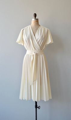 Vintage 1970s ivory semi-sheer polyester dress with wrap bodice, elastic waist, long sash belt and semi-full unpressed pleated skirt. --- M E A S U R E M E N T S --- fits like: small/medium bust: 36-39 waist: 22-30 hip: free length: 44 brand/maker: n/a condition: excellent to ensure a good fit, please read the sizing guide: http://www.etsy.com/shop/DearGolden/policy ✩ more vintage dresses ✩ http://www.etsy.com/shop/DearGolden?sect...