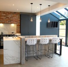 An individually designed kitchen with an industrial twist Cabinetry – painted blue black slab door Work surfaces – Neolith sintered compact surface in calacatta Unique feature – breakfast bar created with lime washed railway sleepers www.nestkitchens.co.uk