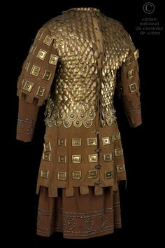 Comedy-French N °:  D-CF-739 B ROLE:  Peer Knight COSTUME DESCRIPTION:  Skin armor doublet lined with metal plates and copper scales on a tunic and skirt in brown wool. BACK