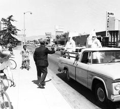 Ku Klux Klan parade, Panorama City, California, September 15, 1966. Children on bicycles watch as Ku Klux Klan members drive south down Van Nuys Boulevard. Photographer and Donor: Ralph Samuels. San Fernando Valley Collection. San Fernando Valley History Digital Library.