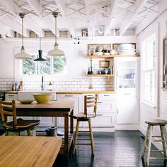 lFarmhouse kitchen with white subway tile, farm sink, barn style lights, and open shelves stacked randomly with vintage dishes and pottery.