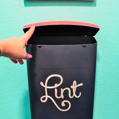 "Wall-Mounted Laundry Room Lint Bin.  LOVE this idea!  I could spray paint one of my millions of containers I have in my cabinets & cut the word ""Lint"" out of vinyl on my Cricut."