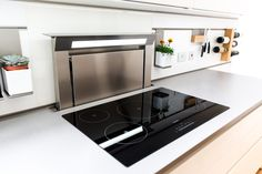 A white matt handleless German kitchen in Alexandra Park, London. The worktop is Silestone and the appliances are Siemens. One of our recent projects. Downdraft Extractor, Alexandra Park, German Kitchen, Stove, Kitchen Design, Kitchen Appliances, Projects, Diy Kitchen Appliances, Log Projects