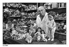 """Docteur Henri Launay - doctor to """"sick"""" dolls. Since 1964 from a storefront in the 11eme in Paris, he's been repairing and restoring old or antique dolls (poupees) - and he wears a labcoat while doing so!"""