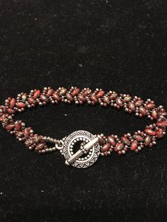Hand beaded super duo and seed bead picasso red bracelet. This gorgeous bracelet is adorned with an antique silver toned sunburst toggle clasp fits sizes 6 1/2-7 1/2